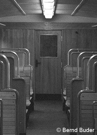Drehtür des Dienstabteiles: Gut erkennbar die sich im Fahrgastraum befindlichen Türscharniere. Der schwarze Punkt rechts ist der in die Wand eingelassene Türstopper (1984).